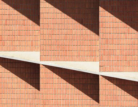 Design of a masonry wall with vertical and diagonal lines. Shades cast on the wall of orange tones.