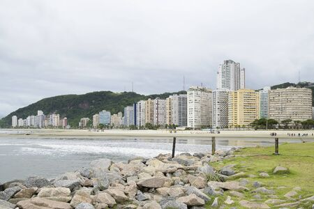 View of a beach of Santos SP Brazil on a cloudy day. Jose Menino beach and the city on background. Brazilian coastal city.