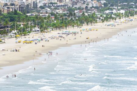 Aerial view of a seafront city, people on the beach on a beautiful day. Cove Beach at Guaruja SP Brazil. Place known as Praia da Enseada. Brazilian coastal city.