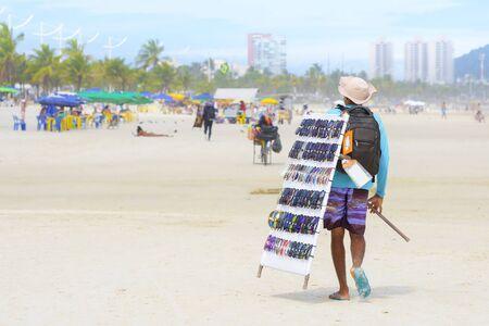 Street vendor selling sunglasses at a brazilian beach.