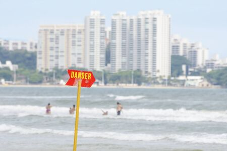 Red warning sign at the beach. Board signaling danger of rough or deep sea.
