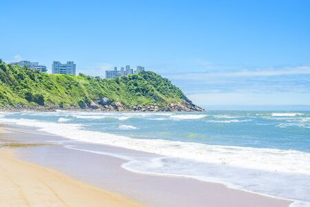 Beautiful Brazilian beach of the Paulista coast on a sunny day. The sea, some waves, the sand and a hill with some buildings on top. Photo at Praia do Tombo beach - Guaruja SP Brazil.