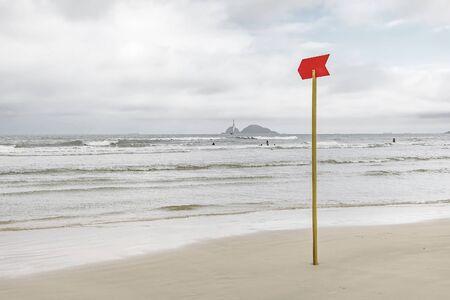 Red danger sign at the beach signaling to sunbathers rough sea or deep sea. Photo taken at Praia da Enseada beach - Guaruja SP Brazil. 版權商用圖片