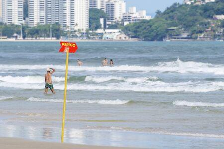 Red warning sign at the beach. Board signaling rough or deep sea. Plaque written in Brazilian portuguese, PERIGO. Photo taken at Praia da Enseada - Guaruja SP Brazil.