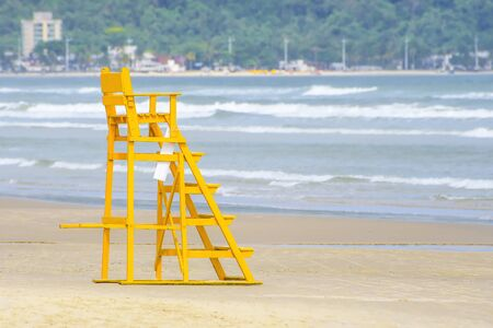 Yellow lifeguard chair at the beach. Tall lifeguard chair to see and do the security of the sunbathers on the sea. Photo taken at Praia da Enseada, Guaruja SP Brazil. 版權商用圖片