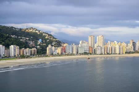 Aerial view of a Brazilian coastal city of the Paulista coast. Praia do Itarare beach, view of Pedra da Feiticeira, The Sorcerer's Stone in english. Border with Santos city and Jose Menino beach.