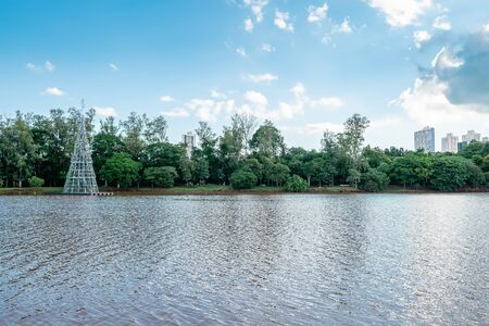 Lake with trees on the lake shore and few buildings on the background. Photo during the day of the Igapo lake, Londrina PR Brazil.