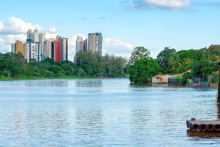 View of a lake with trees on the lake shore and few buildings of the city on the background. City with lot of trees. Photo of the Igapo lake, Londrina PR Brazil.
