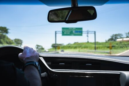 Driving a car on the highway passing by a transit sign. View through the inside of a car during a car trip on a Brazilian road. 版權商用圖片