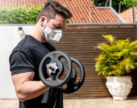 Portrait of a man wearing face mask doing exercises at home during quarantine. Man doing biceps curl with a dumbbell alone at home. 版權商用圖片 - 145670675