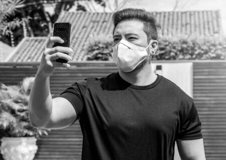 Portrait of a man wearing face mask taking a selfie on the phone. Isolated man at home during quarantine.