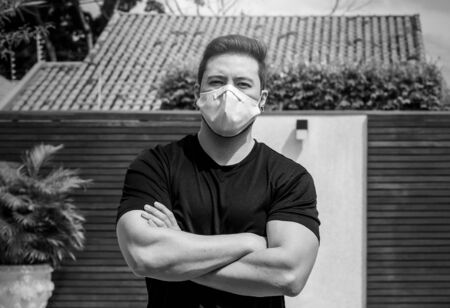 Portrait of an adult man with crossed arms wearing a white face mask during quarantine at home. Black and white photo. 版權商用圖片