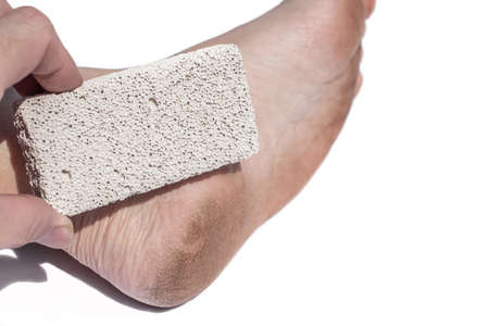 Man cracked heel and a pumice stone, volcanic rock. Dirt cracked feet due to walking barefoot. 版權商用圖片 - 155192662