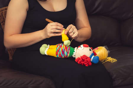Woman seated on the sofa using a knitting needle to sew a crochet clown doll.