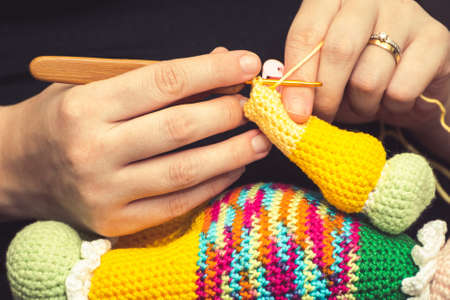 Close up on the hand of a woman using a knitting needle to sew a crochet doll with a woolen yarn.