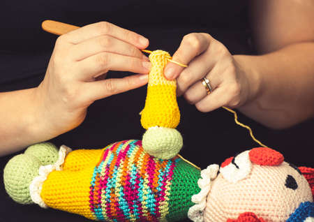 Hand of a woman using a knitting needle to sew a crochet clown doll. Handmade kids toy.