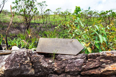 One wooden board indicating the direction to the right, on top of rocks. Path to follow in the woods. Landscape of the Brazilian Cerrado. No writings on the wooden board.