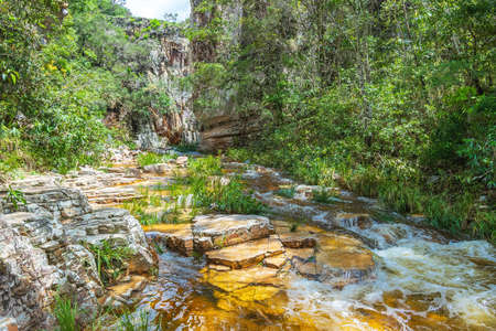 Stream of water from a river passing between two big rocky walls of sedimentary rocks. Water with golden tones because of the rocks. Eco tourism destination of Capitólio MG, Brazil.