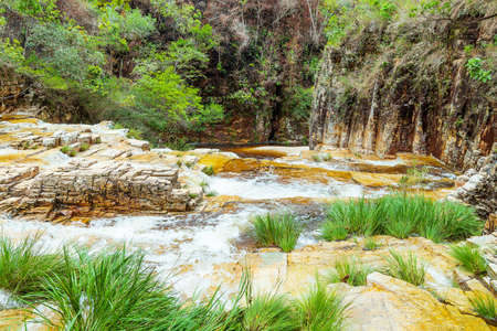 Waterfalls with golden tones, sedimentary rocks and the green vegetation of the Cerrado Mineiro at Capitólio MG, Brazil. Eco tourism destination.