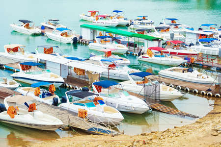 Many tourist speed boats docked at port. Boat rides tourist spot.