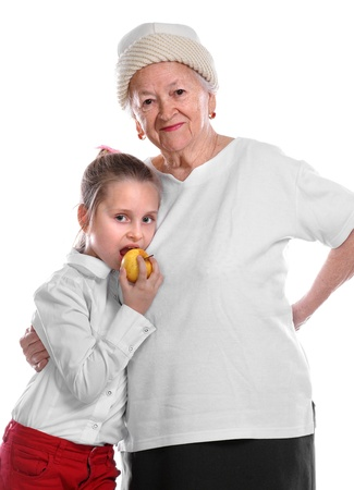 Grandmother and young girl eating an apple smiling and embracing one another on white background Stock Photo - 17017409