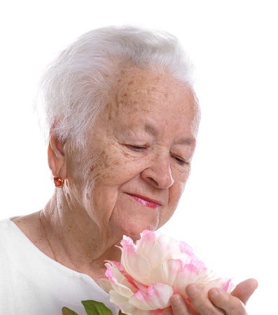 Beautiful old woman with pink flower on a white background 免版税图像