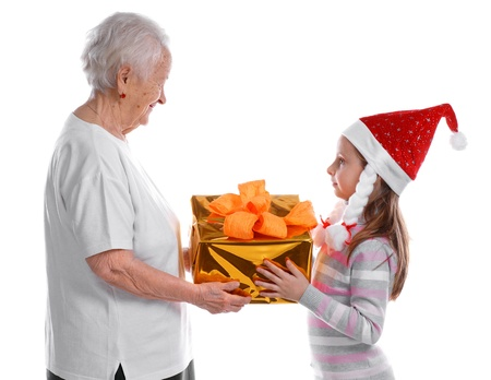 Old woman giving gift box to a little girl in santa hat on white background Stock Photo - 17017408