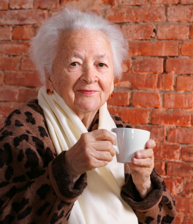 Oude vrouw genieten van koffie of thee beker op bakstenen achtergrond