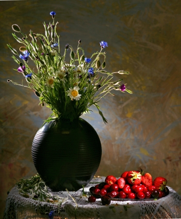 Colorful flower arrangement centerpiece in black vase and fruits on a salver on an abstract background photo