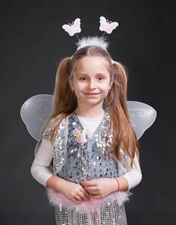 Happy small girl dressed up as a fairy on a gray background Stock Photo - 17017170