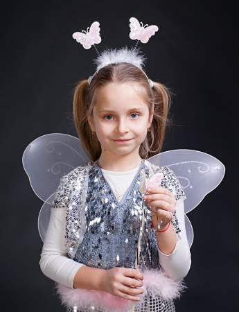 Happy little girl dressed up as a fairy on a gray background Stock Photo - 17017174