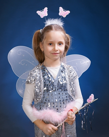 Little girl dressed up as a fairy on a blue background Stock Photo - 17017169