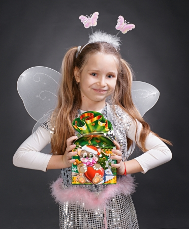 Little girl dressed up as a fairy and holding gift box on a gray background Stock Photo - 17017167