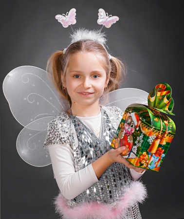 Little girl gressed up as fairy and holding gift box on a gray background Stock Photo - 17017172