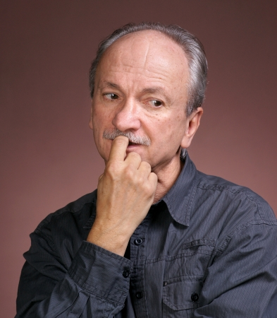incertitude: Portrait of a senior man biting nails on a brown background Stock Photo