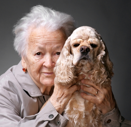 Close-up portret van een oude vrouw met Amerikaanse spaniel op een grijze achtergrond