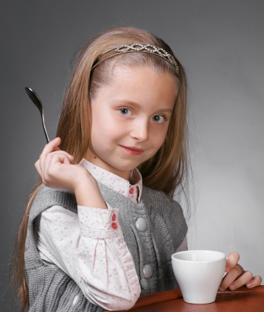 Little girl with cup of tea holding a spoon in hand on a gray ackground Stock Photo - 17016948
