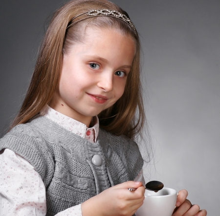 Little girl with cup of tea holding a spoon in hand on a gray ackground Stock Photo - 17016947