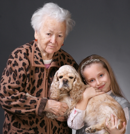 Old woman with her granddaughter and a dog (american spaniel) on a gray background Stock Photo - 17016959