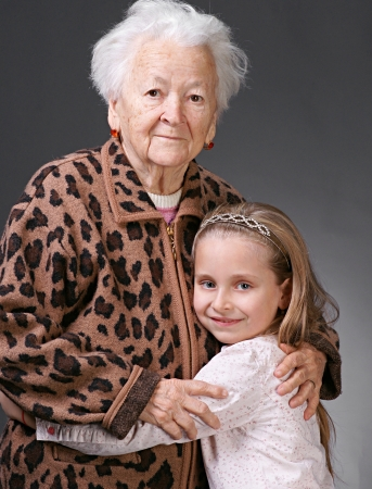 Closeup portrait of senior woman with little granddaughter on a gray background background  Stock Photo - 17016957