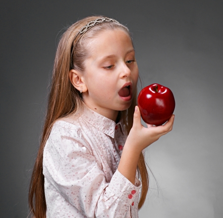 Little girl with red apple on gray backround Stock Photo - 17038383