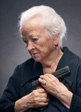 marksman: Old woman with pistol on a gray background Stock Photo