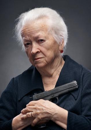 Close-up portret van oude vrouw met pistool op een grijze achtergrond Stockfoto