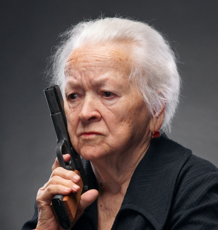 Close-up portrait of angry old woman with pistol on gray background Stock Photo - 17062878