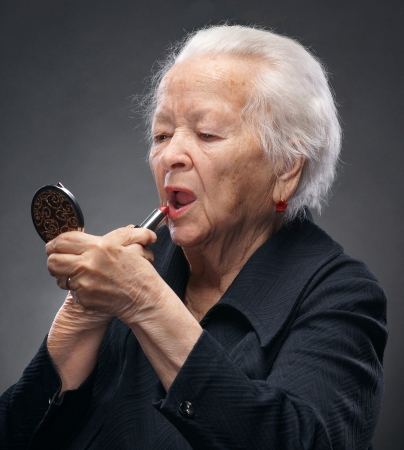 Closeup portrait of old woman with lipstick and mirror on a gray background