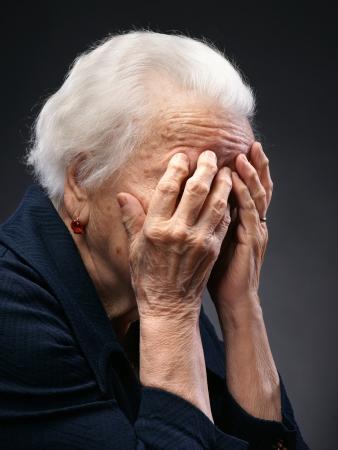 sgomento: Infelice donna anziana senior con mani al viso su uno sfondo grigio Archivio Fotografico