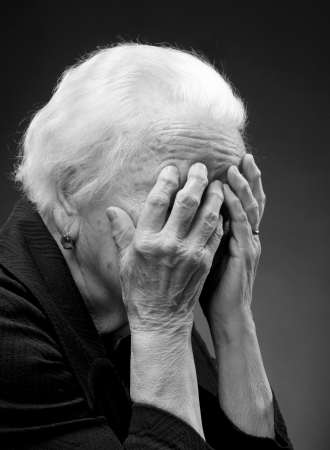B w portrait of unhappy old woman with hands to her face on a gray background