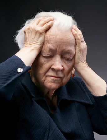 Portret van een trieste oude vrouw die haar hoofd geïsoleerd tegen grijze Stockfoto