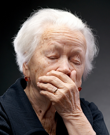 Old sad woman on a gray background Standard-Bild