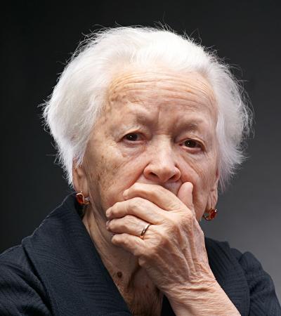 Oude droevige vrouw met hand op haar gezicht op een grijze achtergrond